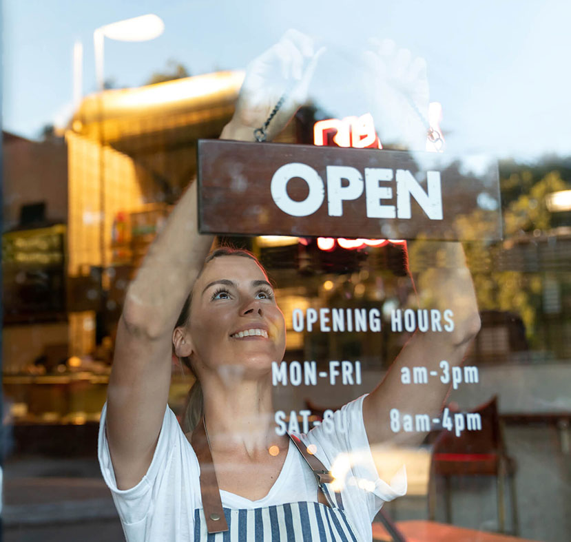 A girl hanging up a window shop photo saying open, with the open hours scheduled below her